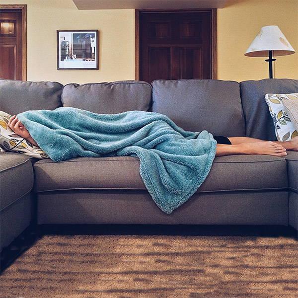 Frau versteckt sich erschöpft unter einer türkisfarbenen Decke auf der Couch