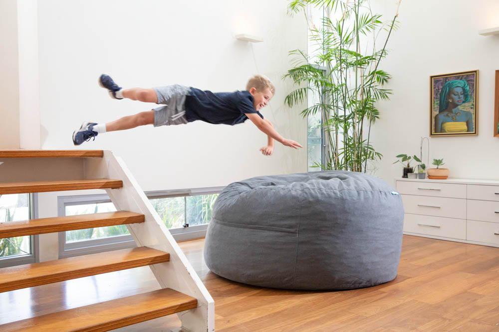 Child jumping into big grey foam filled bean bag