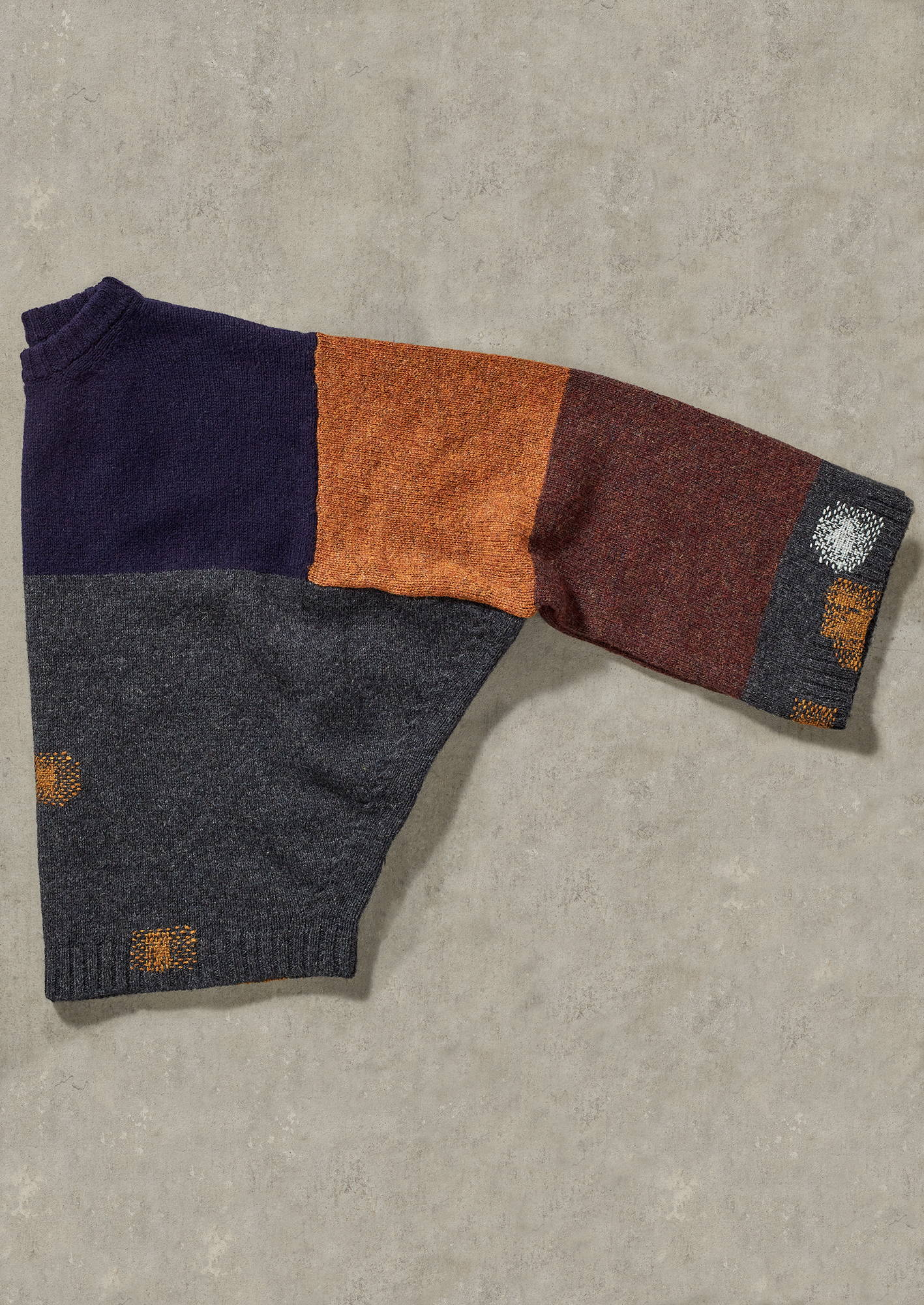 Multicolor sweater from TOAST with mended parts.