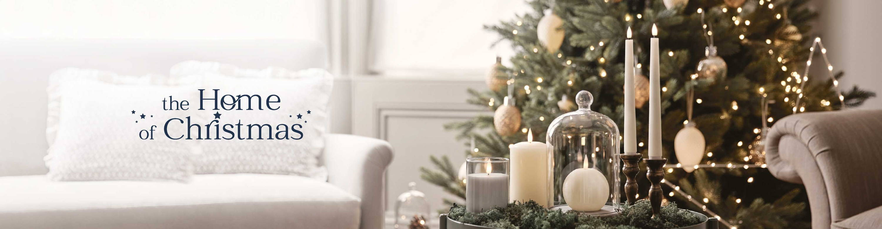 The Home of Christmas living room with a Christmas tree lit with warm white lights, candles and stars