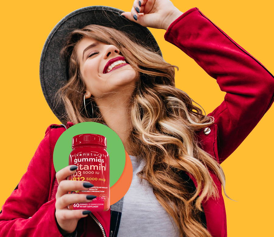 woman smiling in front of bright yellow background holding a bottle of viva naturals vitamin gummies