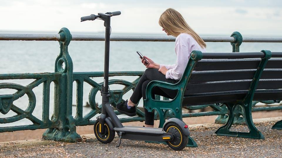 Ninebot Max G30 電動滑板車坐在海邊的長凳上
