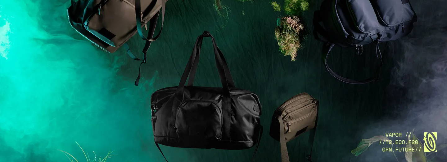 Image of Vapor Collection products floating in a dark room with mist in the background. The Vapor Tote, Vapor Duffel, Vapor Crossbody, are all featured with plants also floating. Copy reads: VAPOR // // T2.ECO.F20 GRN.FUTURE //