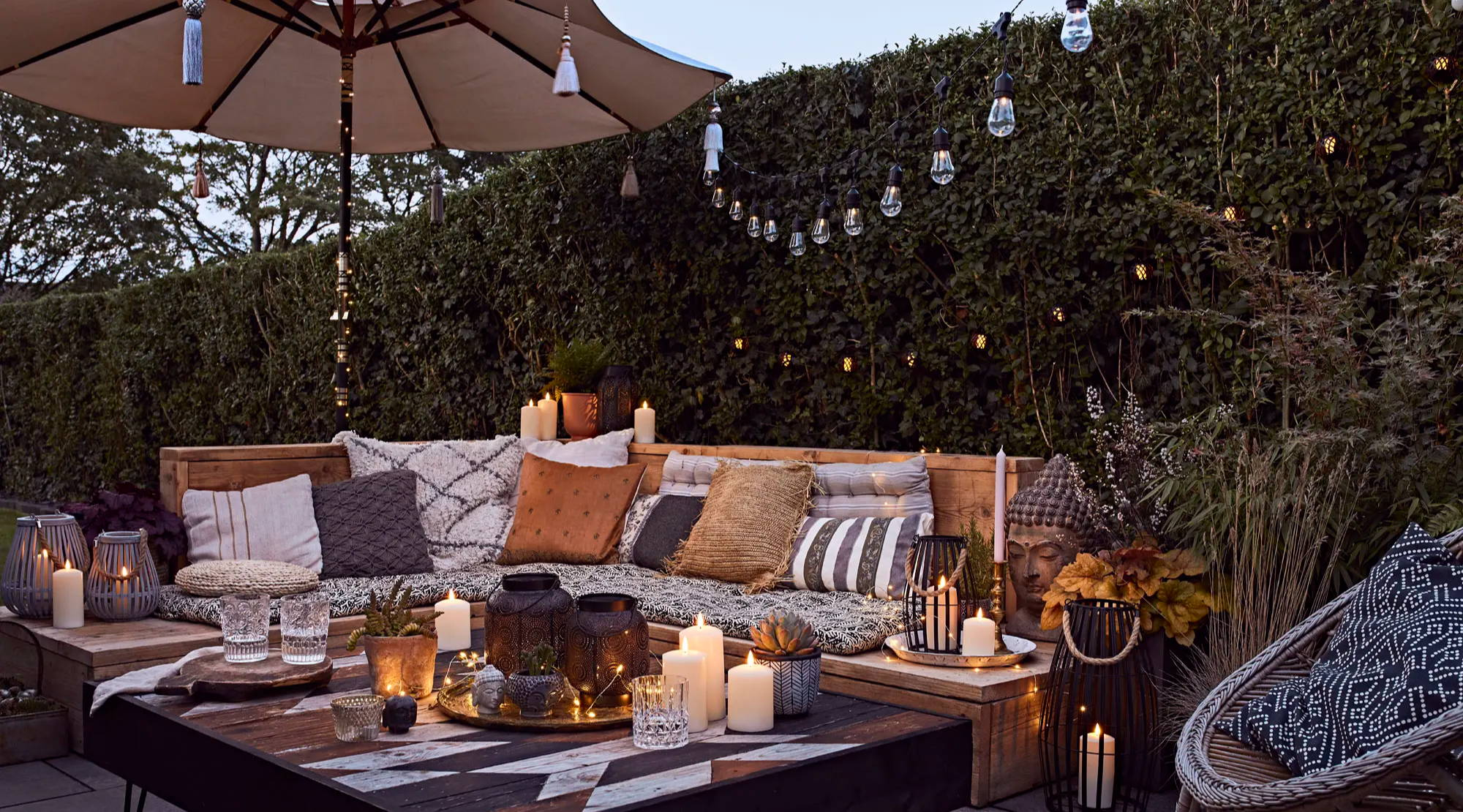 Outdoor space illuminated at night by festoons, candles and lanterns.