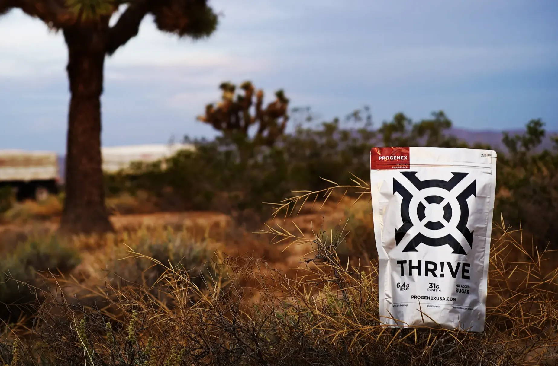 Bag of Thrive in a field with a tree.