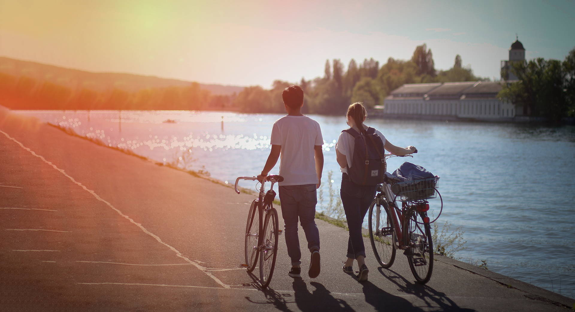 2 bicyclist leading their bikes