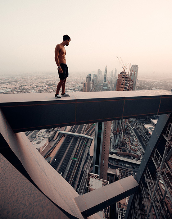 shirtless man standing on beam on top of city building