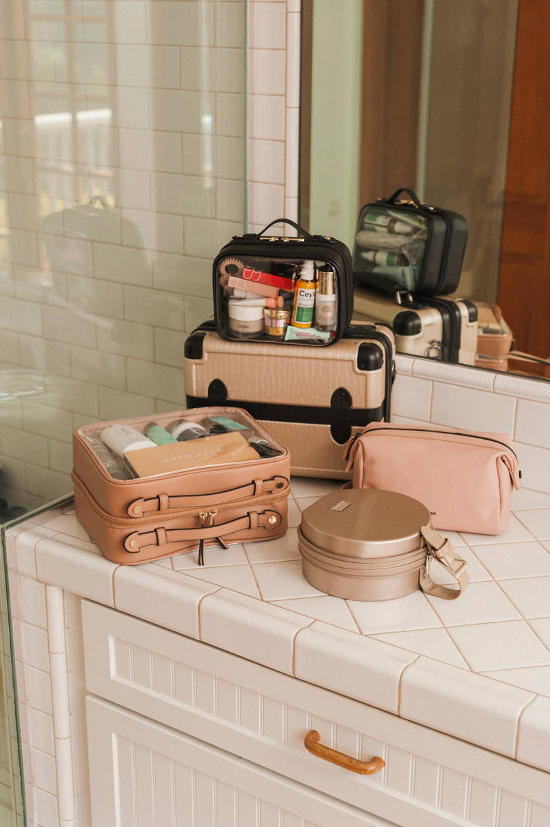 CALPAK Clear Cosmetics Case in Caramel, Baye Mini in Gold, Hue Toiletry Bag in Pink Sand, Vanity Case in Trnk Nude, and Mini Clear Cosmetics Case in Black.