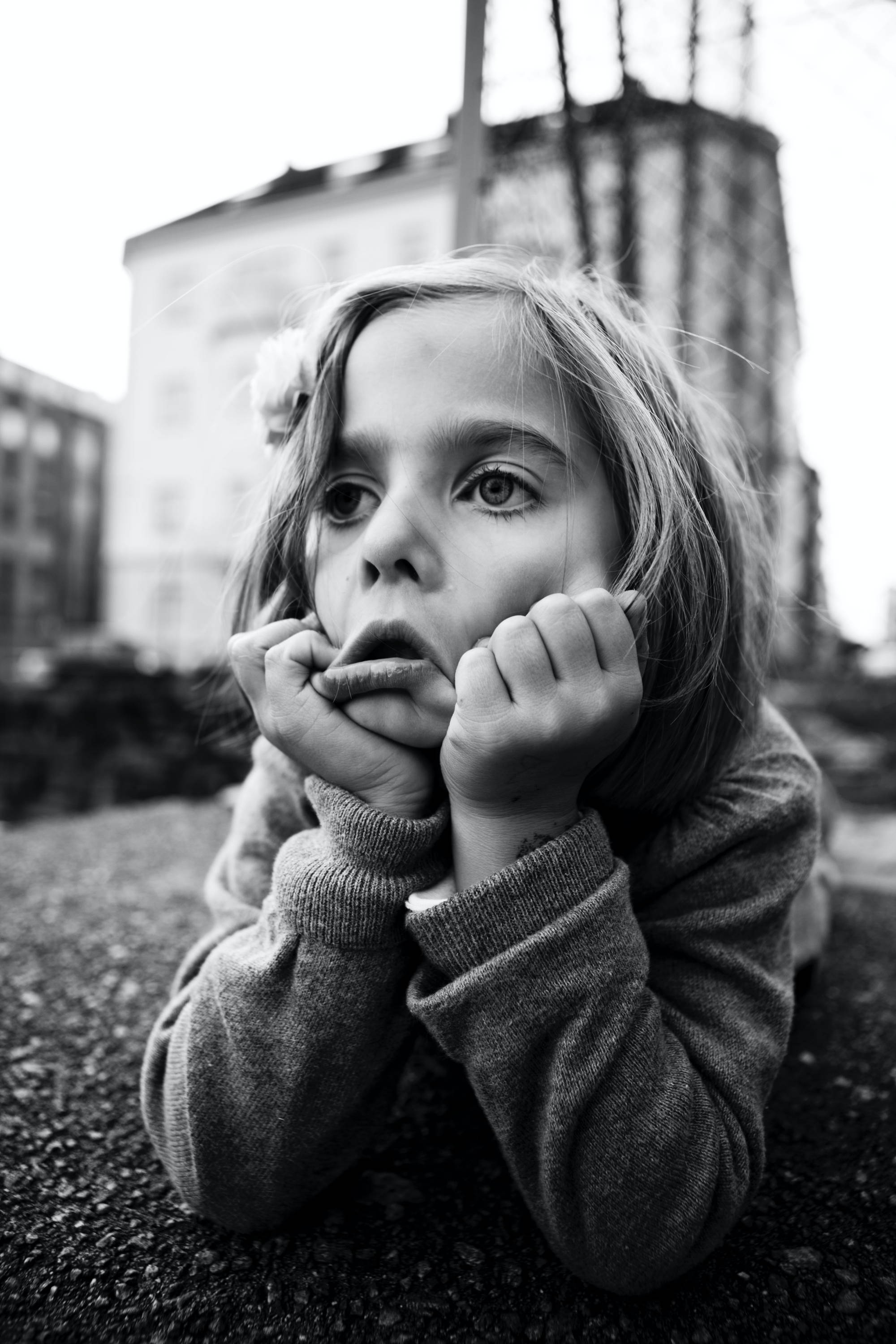 Black and white photo of a little girl resting her head in her hands looking anxious.