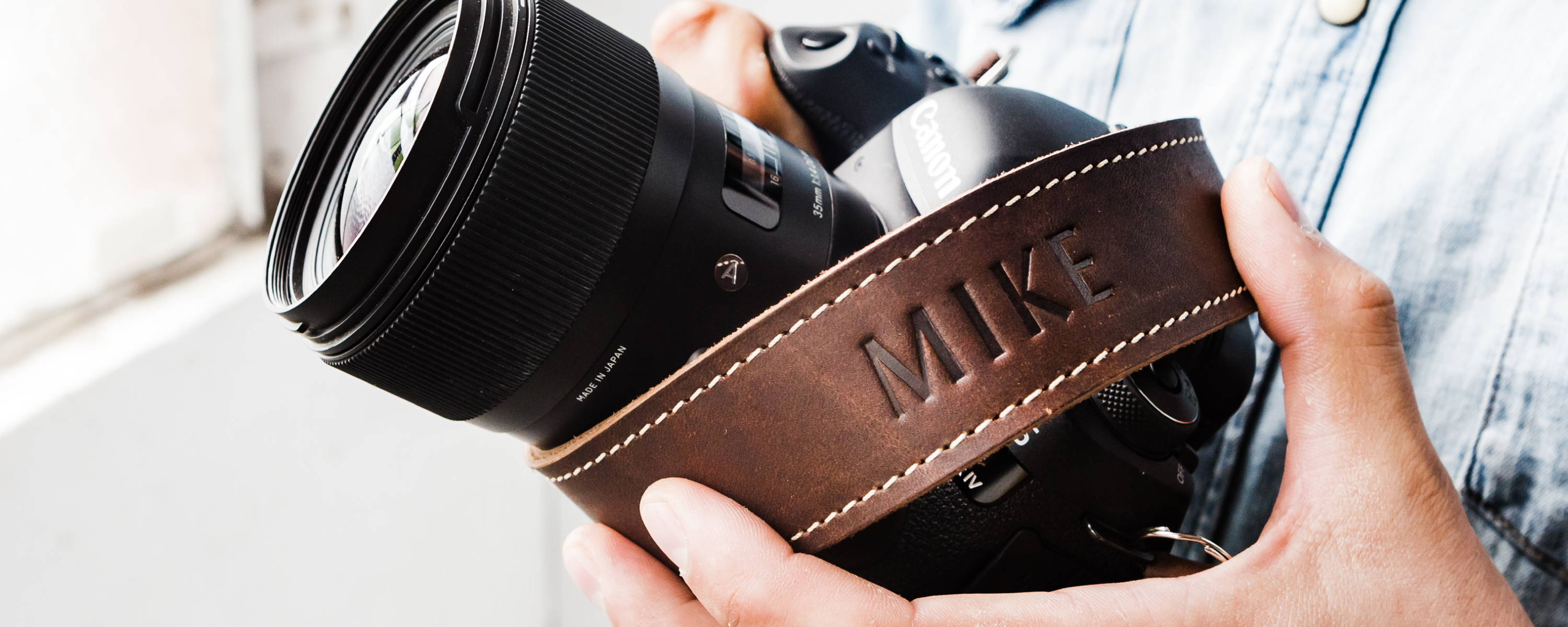 leather camera strap in grizzly brown wrapped around a digital camera