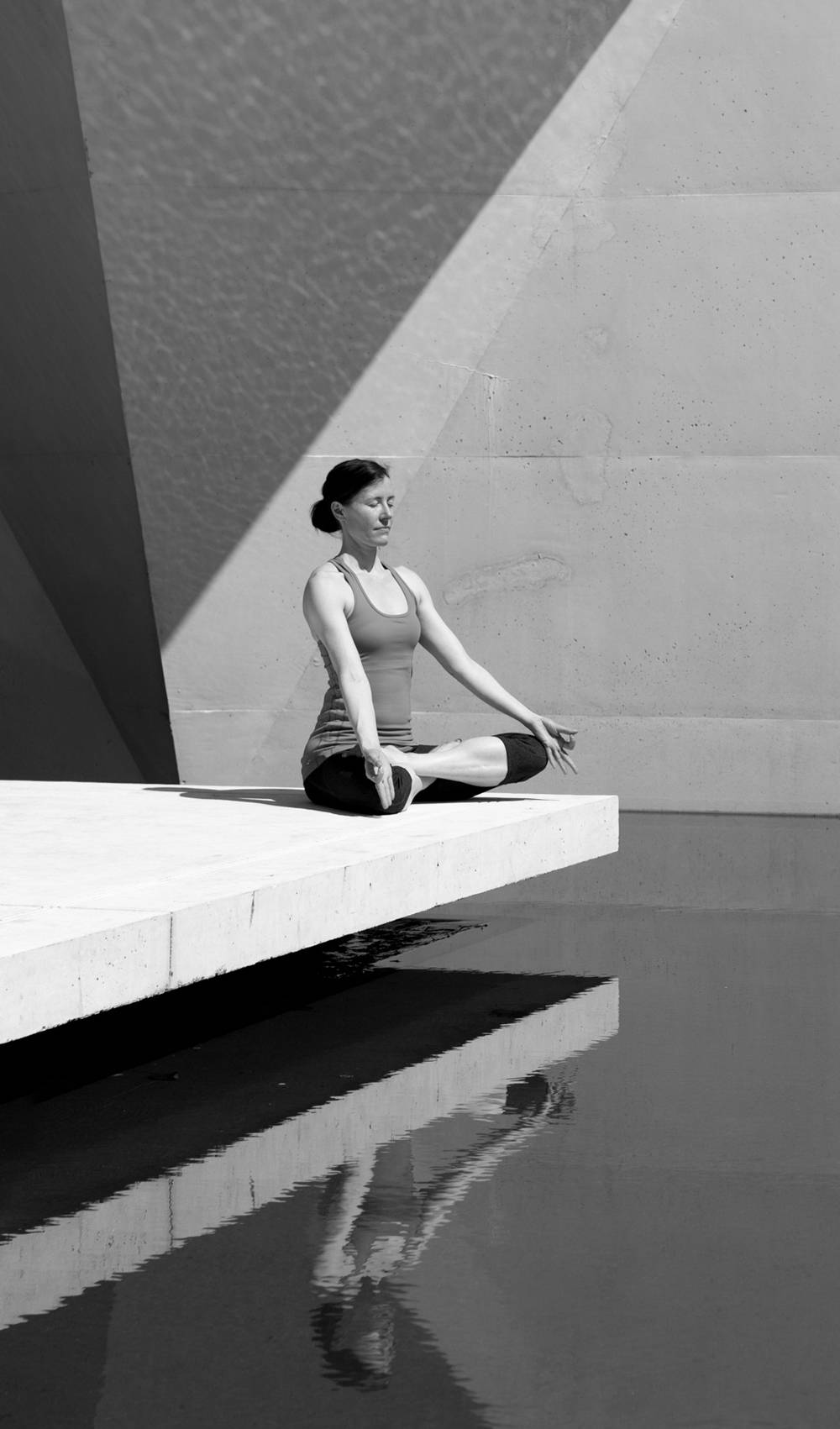 Woman in yoga position sitting over water