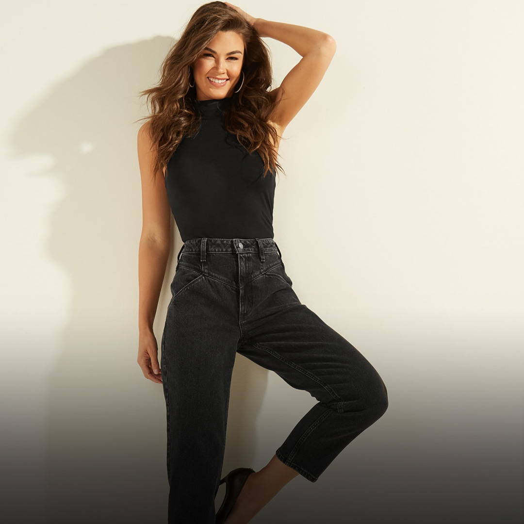 A woman wearing black GUESS denim jeans and a black GUESS top
