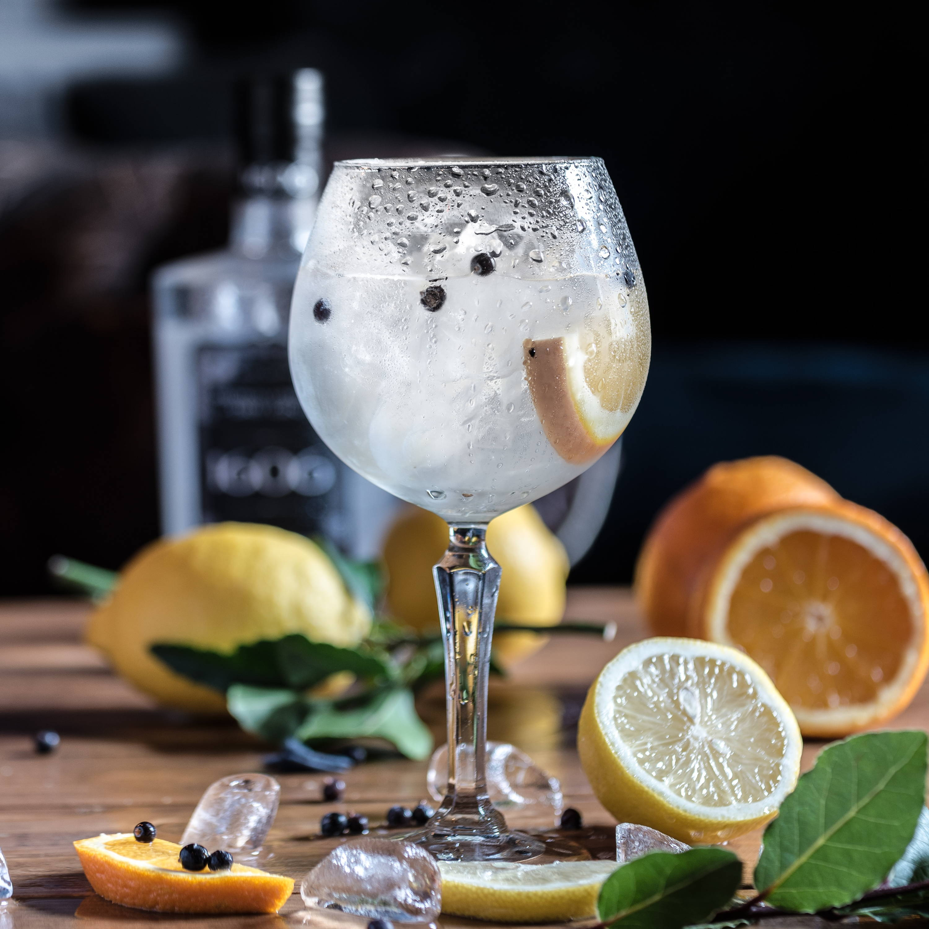 A gin & tonic in a wine glass with an orange slice and juniper berries, on a wooden table with cut citrus, leaves, and berries