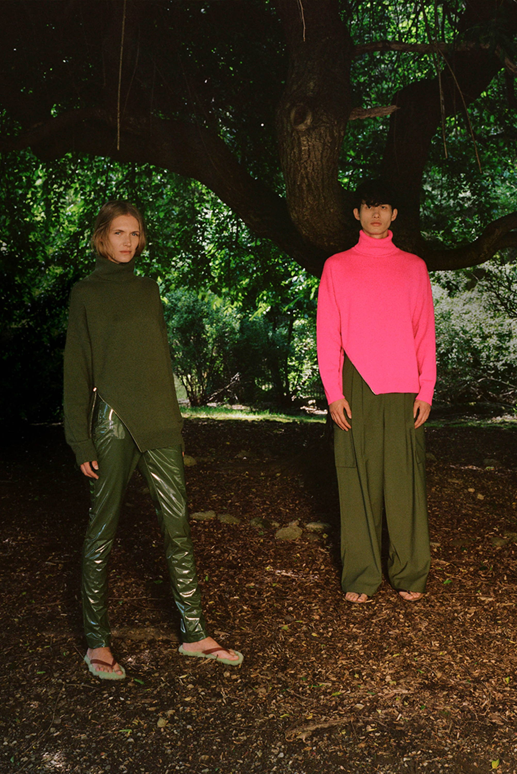 Two models standing under a tree. One model is wearing a green sweater and green tech patent pants. Male model is wearing hot pink sweater and green cargo pants.