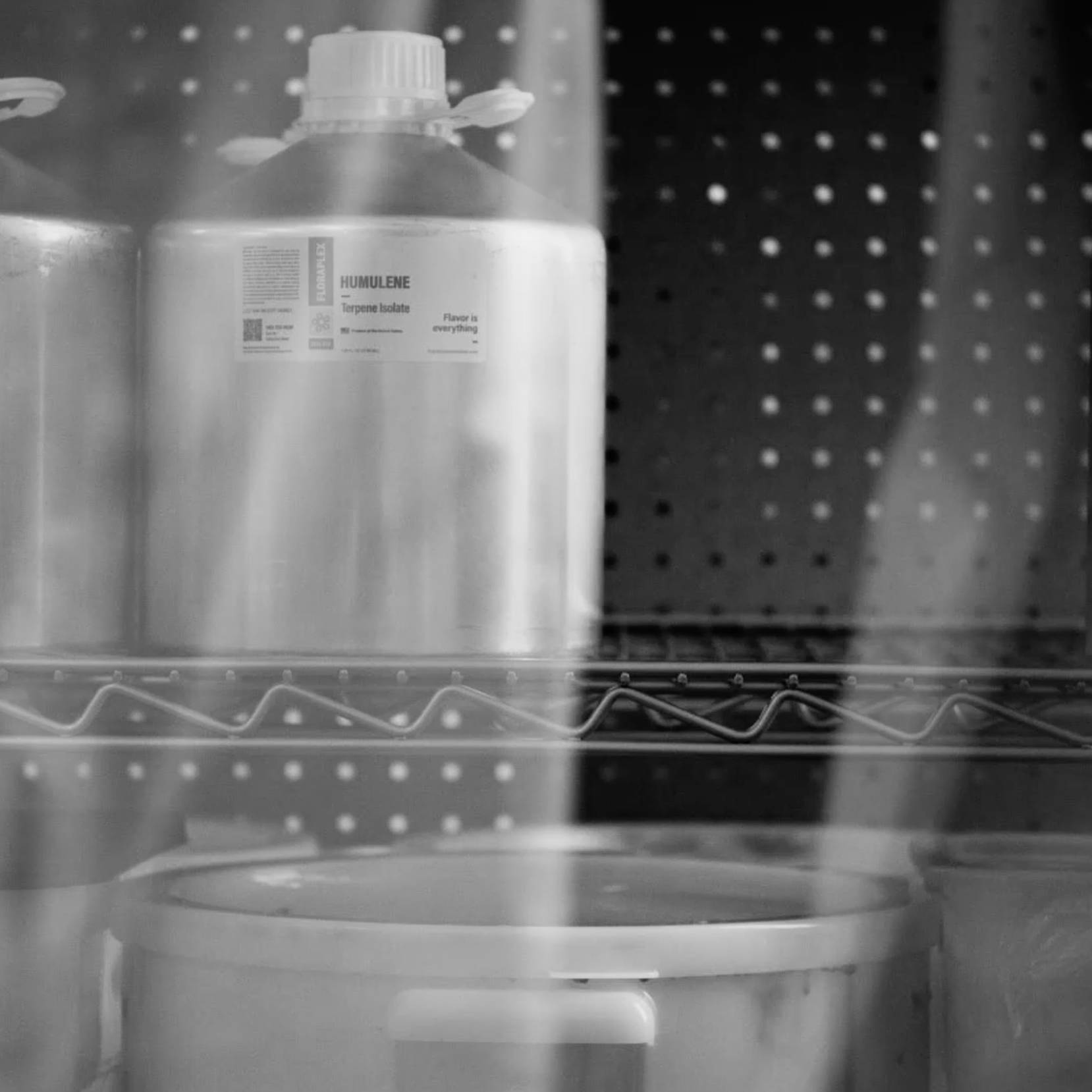 Black and white shot terpene jars in a hemp processing facility