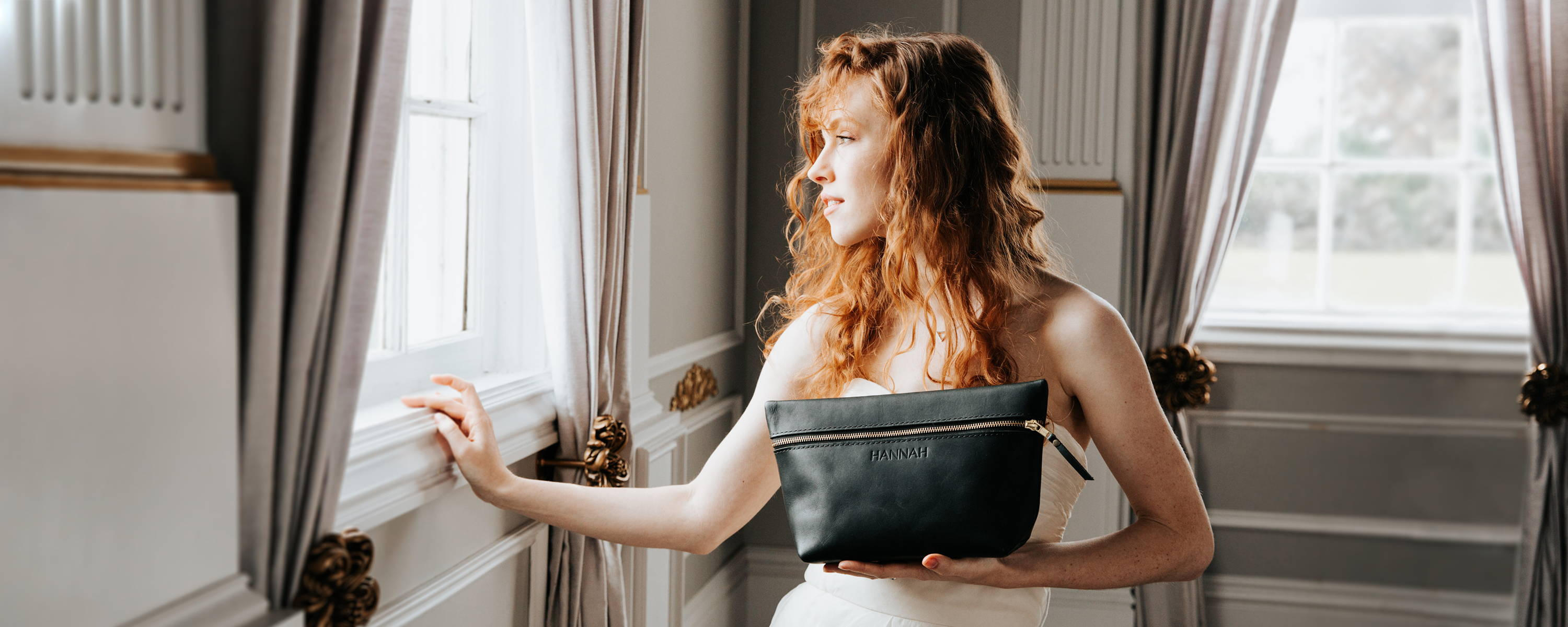 a beautiful bride holding a handmade leather makeup bag and smiling while looking out of a sunlit window