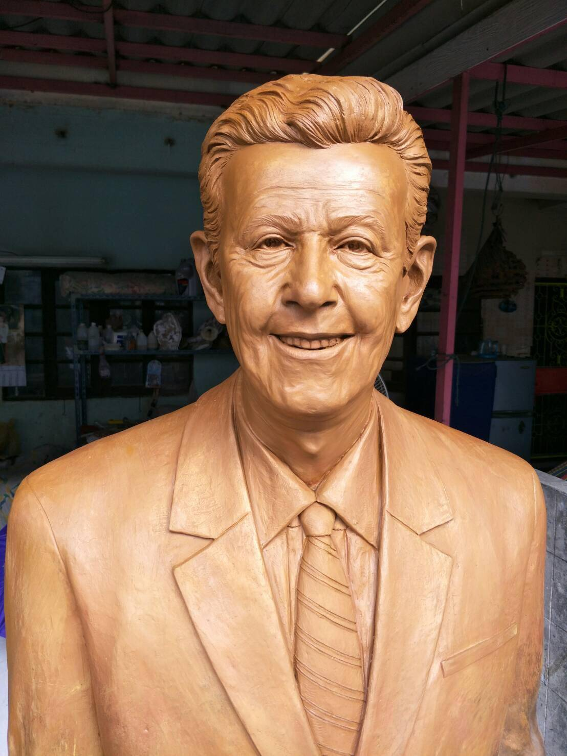 A cast of a man wearing a suit and smiling