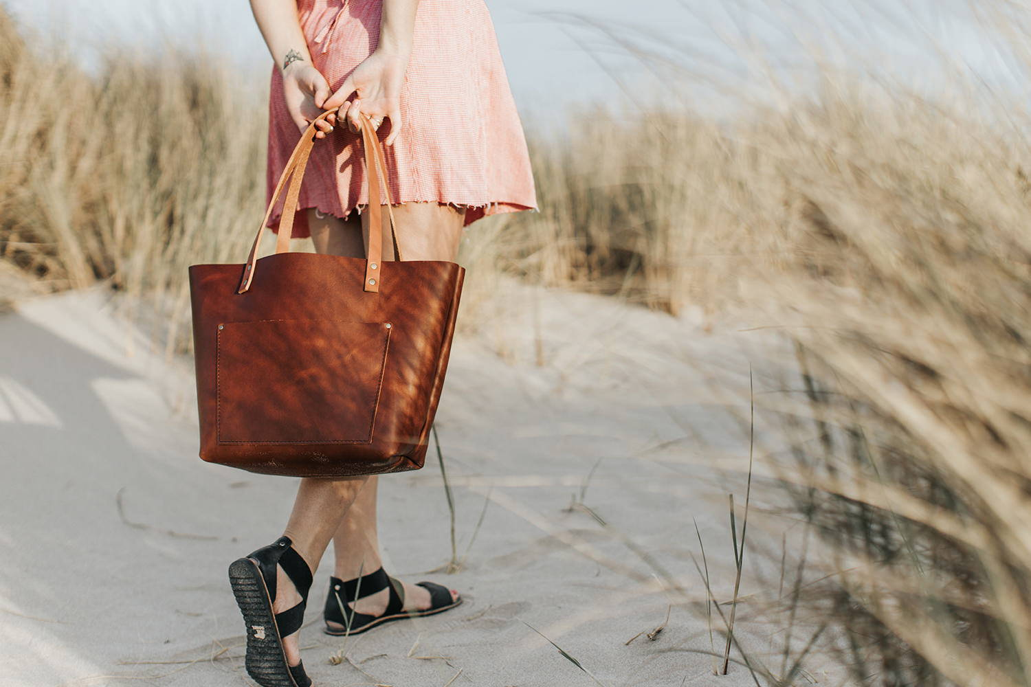 Girl holding a beautiful leather tote on a beach