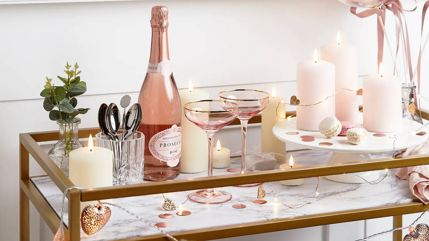 Valentines day table with LED candles, micro heart lights displayed with prosecco and glasses sat on table