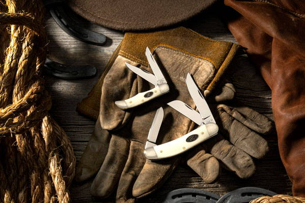 Natural Bone CV Sowbelly and Pocket Hunter Knives on work gloves with cowboy hat and rope.
