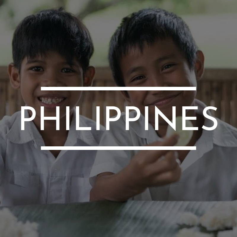 """PHILIPPINES"" Is written on top of an image of two young boys sitting together wearing white."