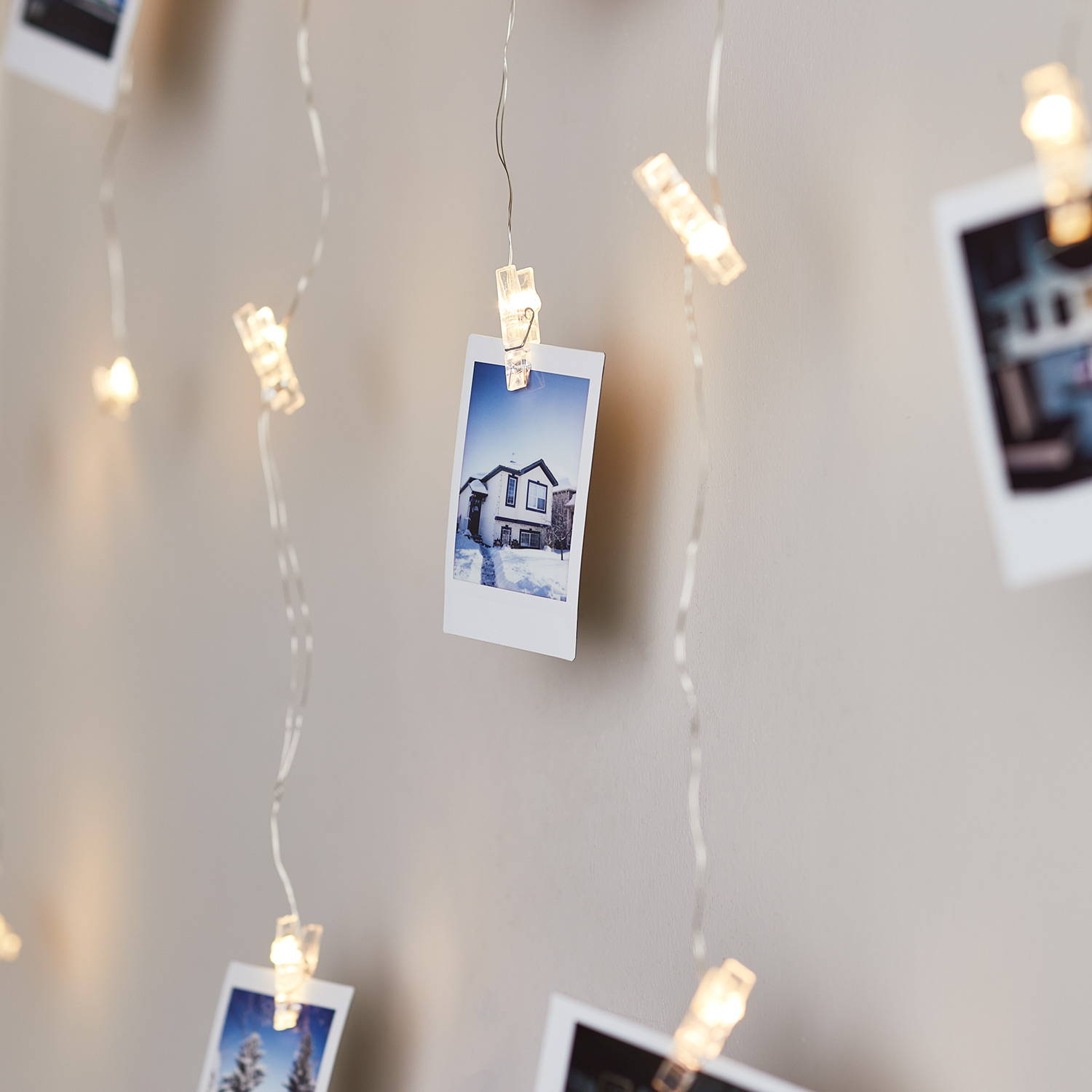 Close up of peg fairy lights illuminated draped across wall with images attached
