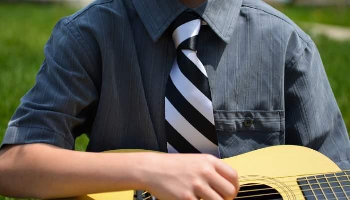 Boy wearing striped tie playing guitar