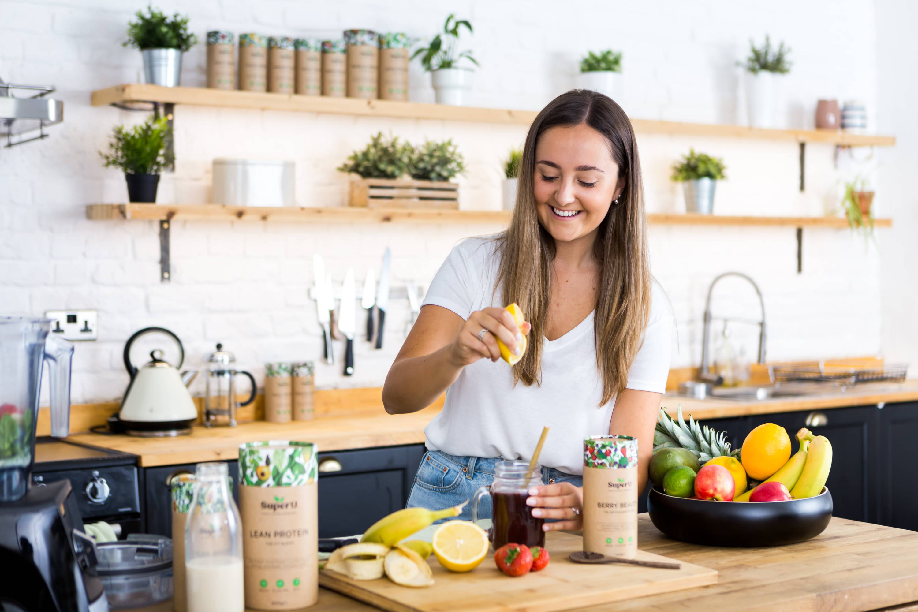 healthy girl making a nutritious vegan smoothie  with fresh fruit and super u superfood blends