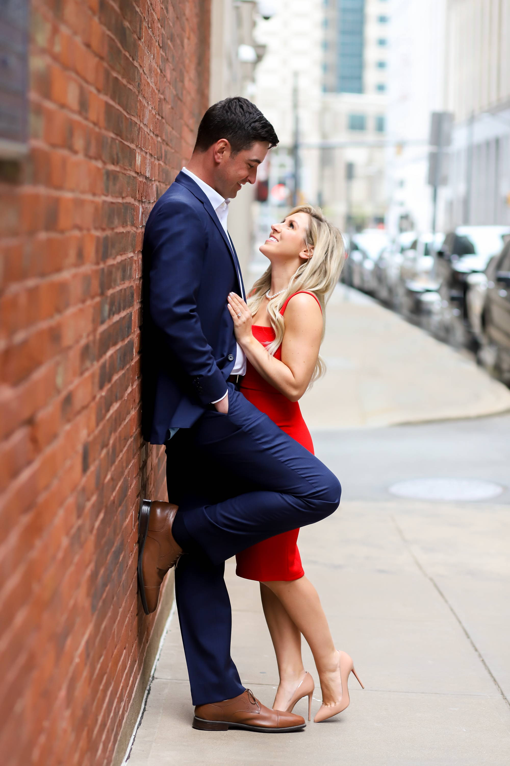 Henne Engagement Ring Couple Standing Next to a Brick Wall and Gazing at Each Other Lovingly