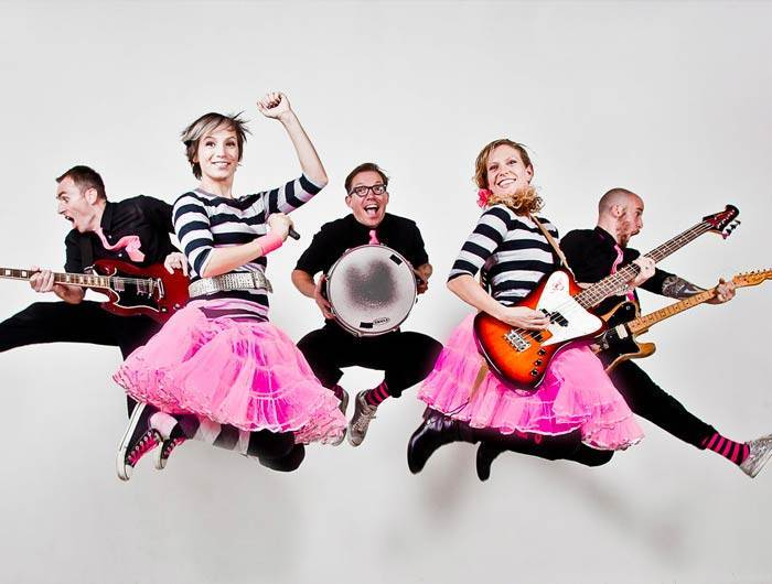 Band in black and hot pink jumping with instruments