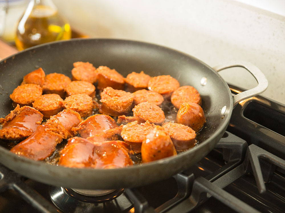 sausages frying in a pan