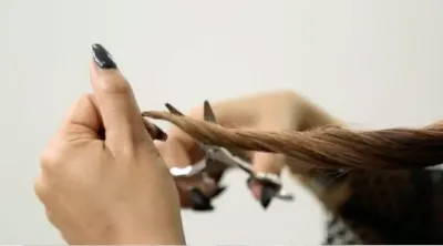 Woman cutting her split ends off her hair