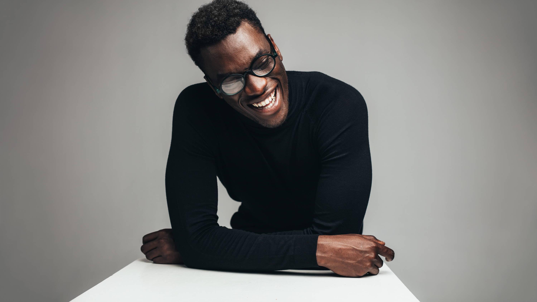 Man in trendy glasses laughs while wearing a sleek, simple black turtleneck
