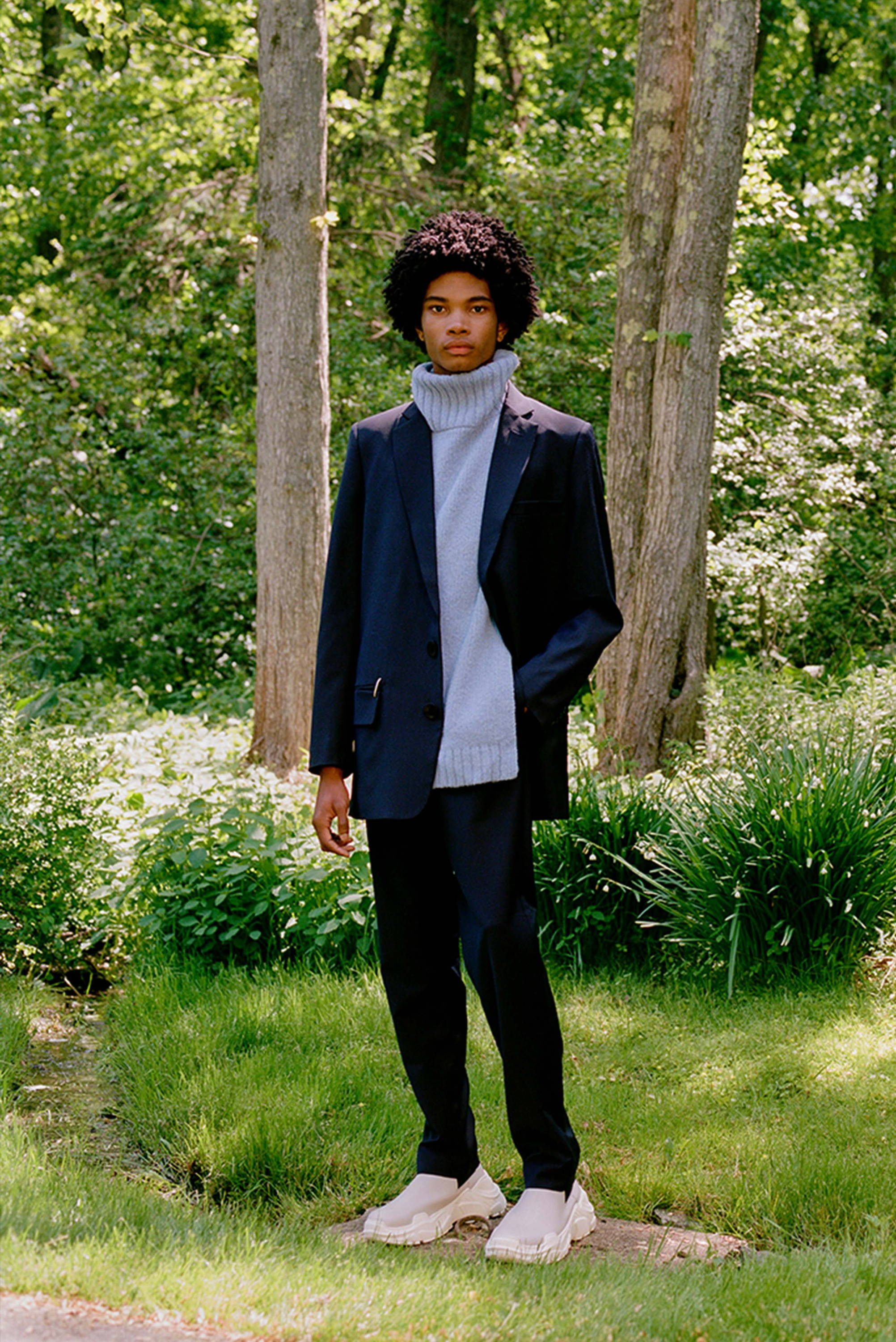 Male model standing on front of woods wearing blue turtleneck dickie and navy blue suit.