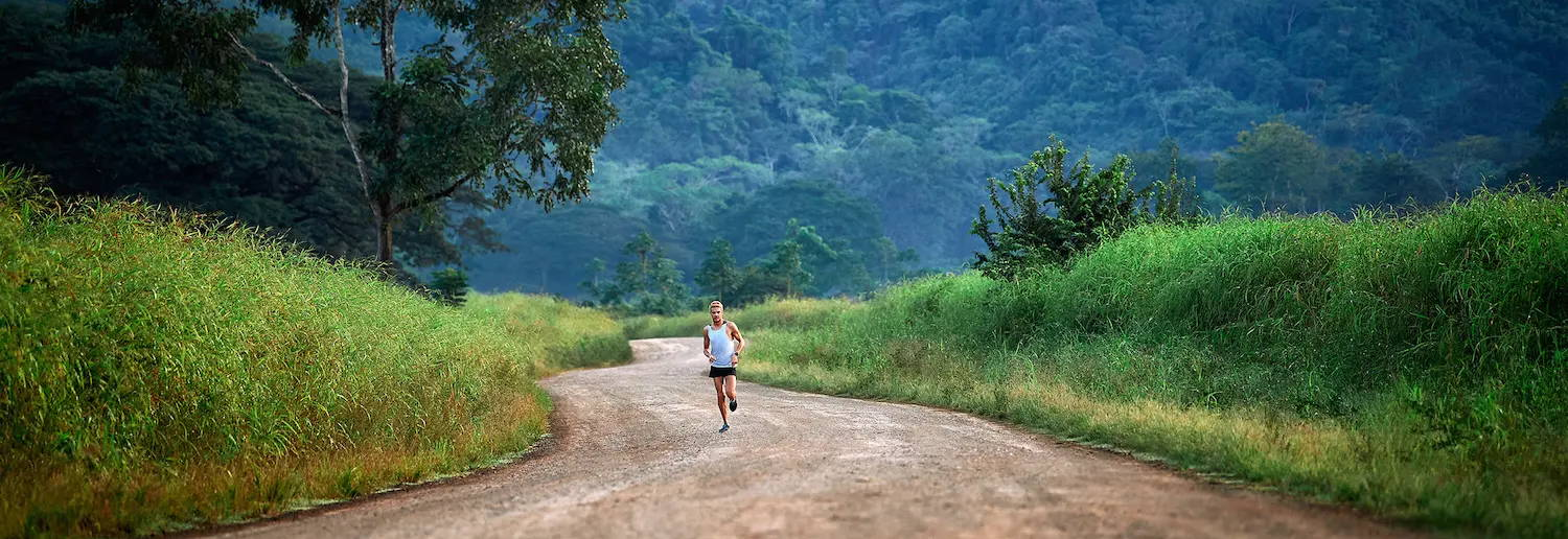 Runner on a dirt road in the mountains and rainforest