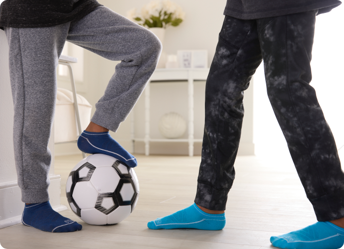 Two boys one wearing dark blue Nn+ ankle socks and the other wearing lighter blue Nn+ ankle socks, playing with soccer ball.