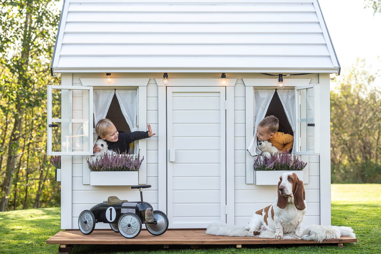 Wooden Playhouse in white color with two boys playing and a car and a dog infront by WholeWoodPlayhouses