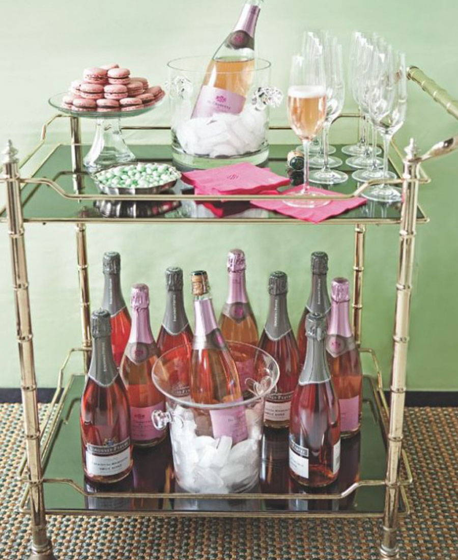 A gold bar cart with pink champagne bottles on the bottom  shelf and champagne flutes with pink macarons on top shelf.