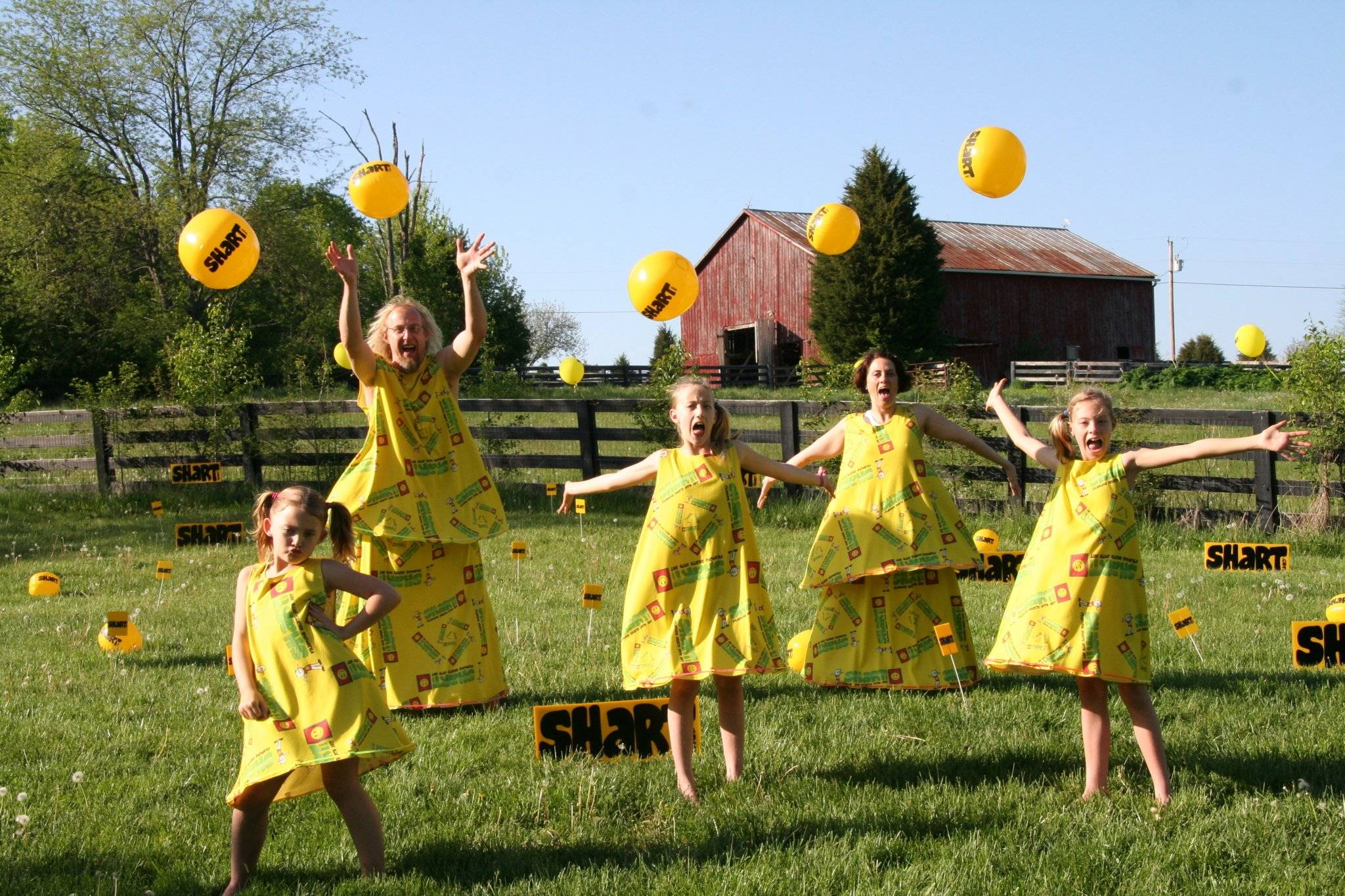 The Shart Family in a field in Bright Yellow Shart Gowns jumping and throwing Shart.com beachballs in the air