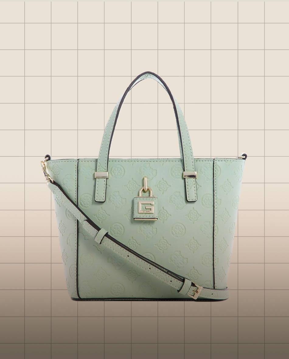 pale green GUESS mini tote handbag on a grid backgrounf
