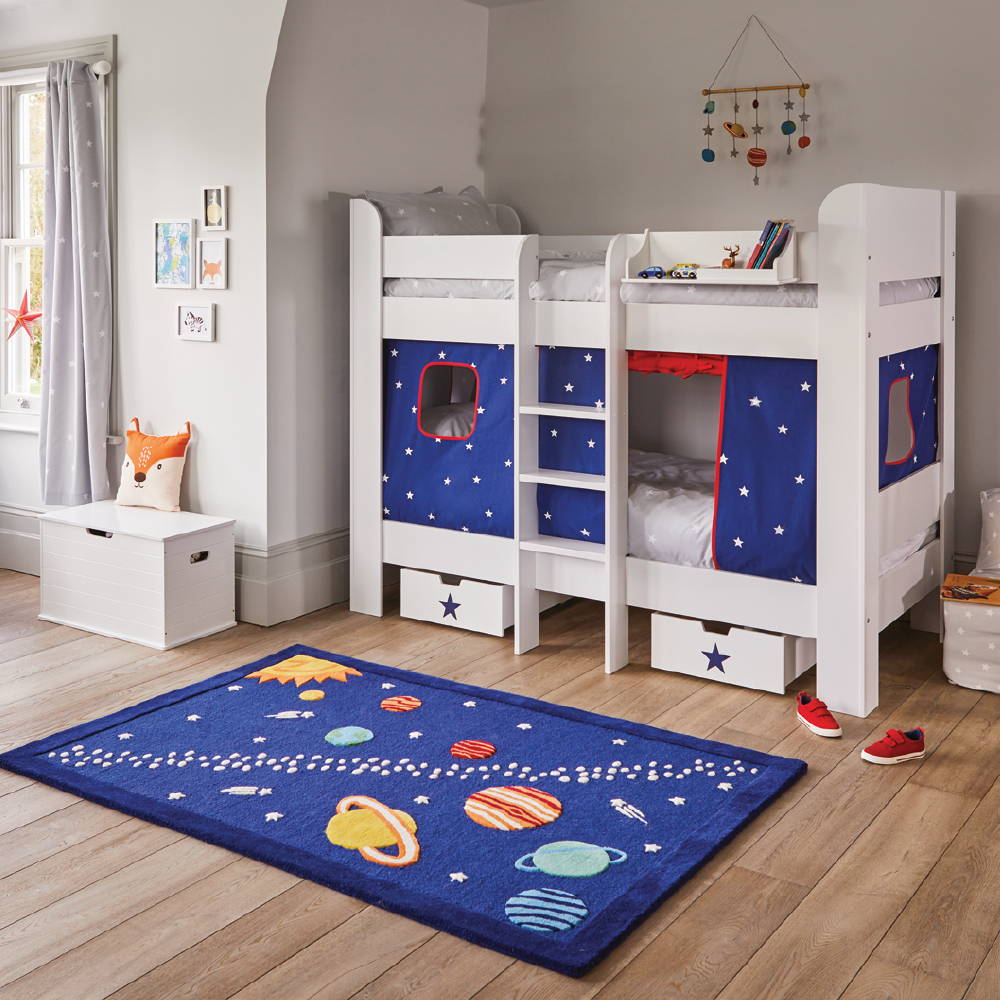 White bunk bed with navy stardust play curtain and space print rug