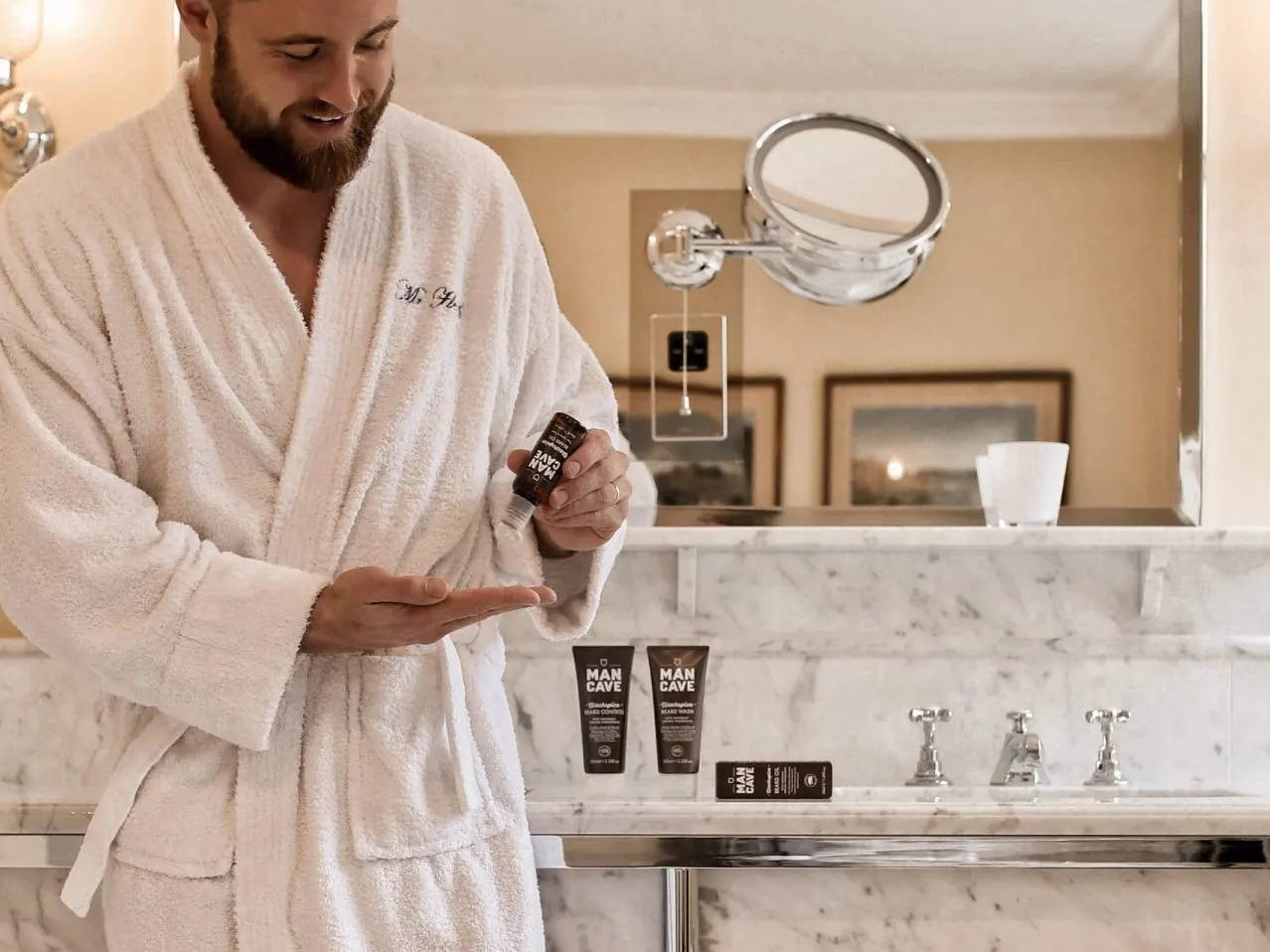 The ManCave Beard Oil being squeezed onto a mans palm in a bath robe with the ManCave blackspice beard control and beard wash on the side of the bathroom sink.
