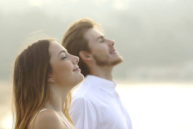 Man and woman with eyes closed head tilted back, smiling and breathing.