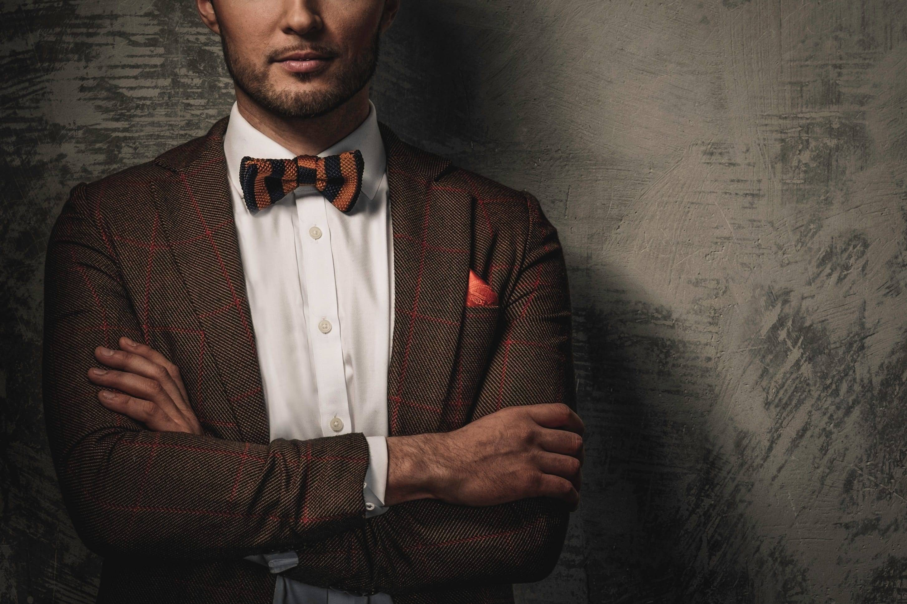 Man in textured windowpane suit and bowtie poses with arms crossed