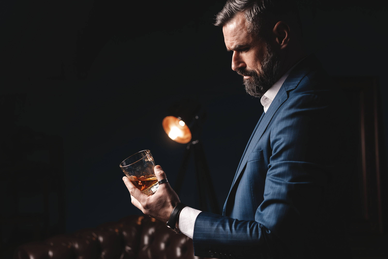 Mr. Connoisseur Classic dressed man in pinstripe suit appreciates a fine drink