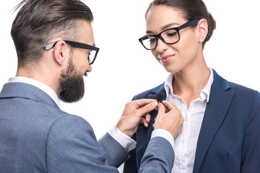 Homme accrochant le microphone à pince à cravate sur le costume d'un collègue