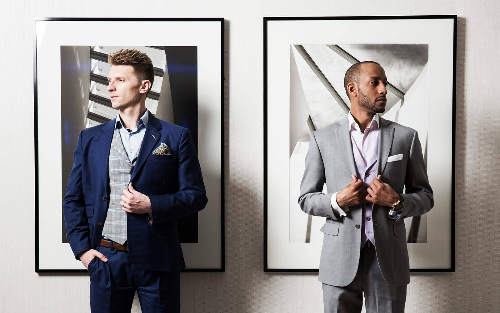 Two elegantly suited young men pose in bespoke suits facing away from each other