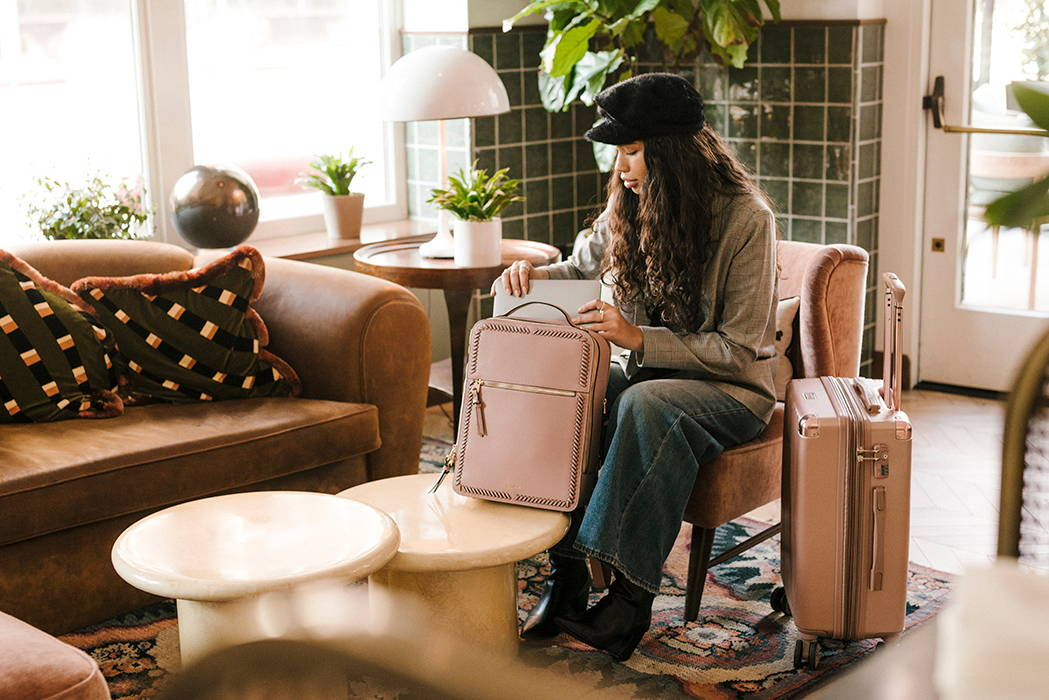 Model shown inserting laptop in to the Kaya Laptop Backpack in Mauve, alongside the Ambeur Carry-on Luggage in Rose Gold