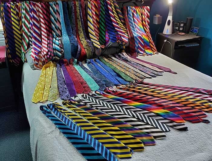 Large collection of neckties displayed on a bed