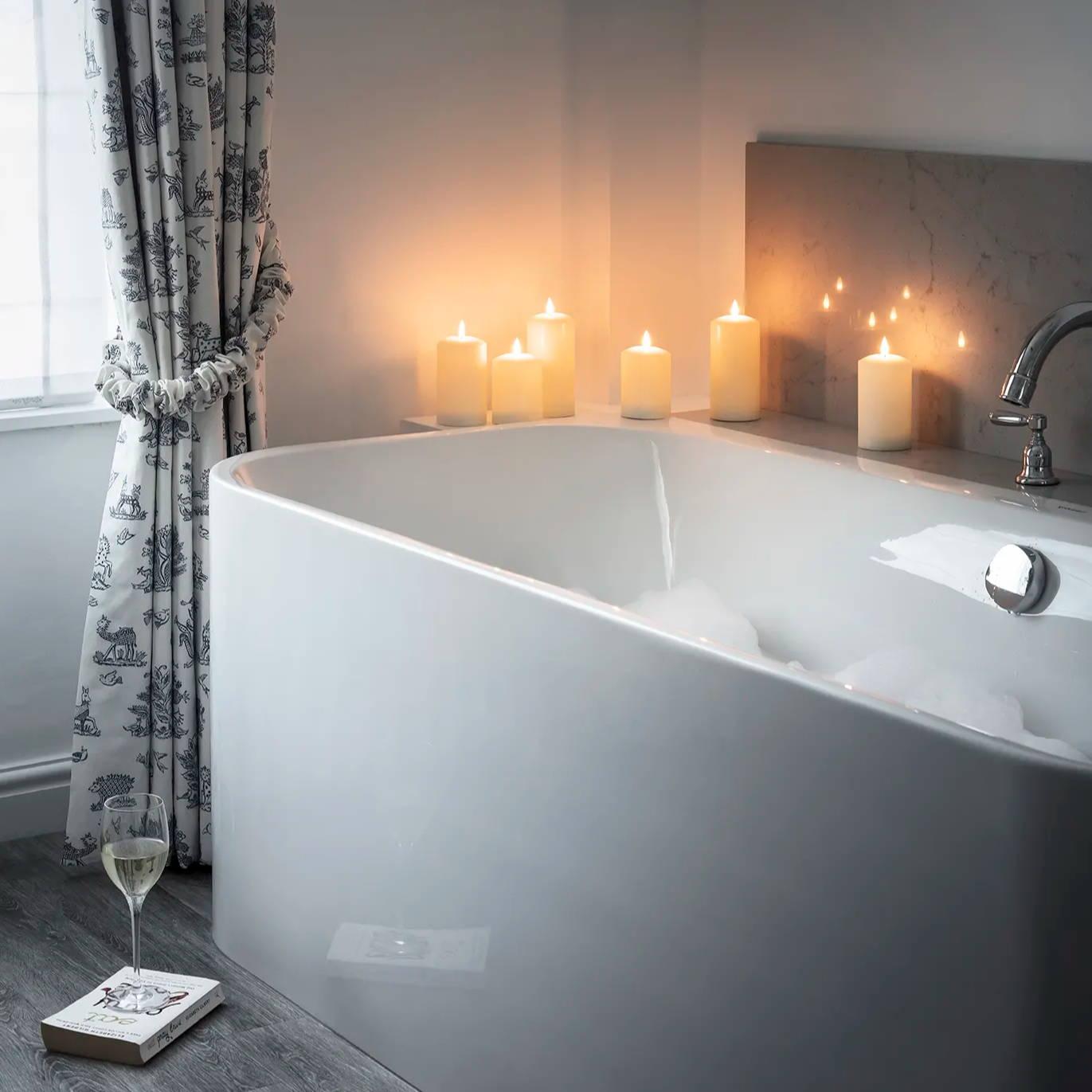 Weiße TruGlow LED Kerzen als Badeimmerdeko mit Badewanne und Fenster.